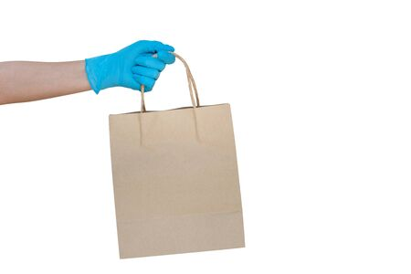 Hand wearing blue glove for protect allergic reaction or infectious diseases coronavirus/covid-19 holding paper bag deliver goods to customer isolated on white background