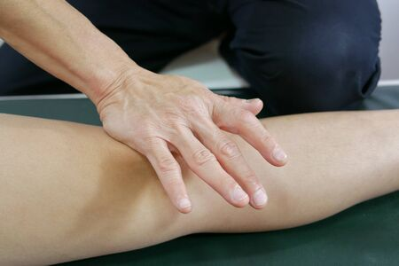 Physical therapist's hand treat patient's knee to decrease pain and improve mobility on medical bed Reklamní fotografie