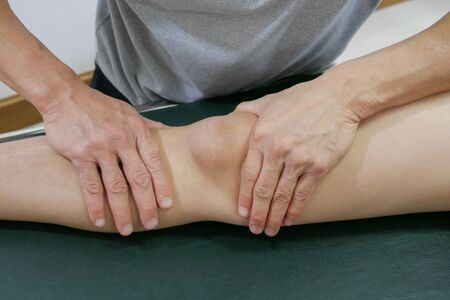 Physical therapist's hands treat patient's knee to decrease pain and improve mobility on medical bed Reklamní fotografie