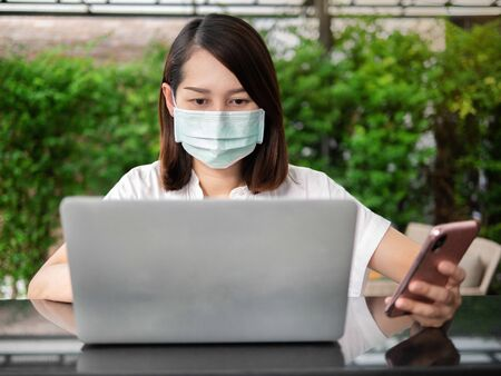 Young Asian woman wearing green medical mask working social distance with computer laptop and mobile phone at home garden background Reklamní fotografie