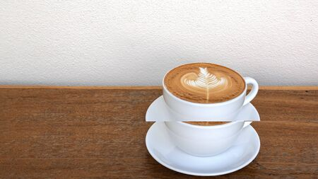 Hot coffee cappuccino latte art foam milk foam on wooden table over white concrete wall texture background