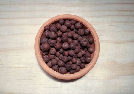 pepper in clay bowl on wooden surface. top view. (allspice, Jamaica pepper)