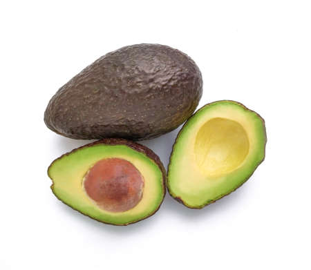 Hass avocado pear (Persea americana) halved and whole on white background with top view