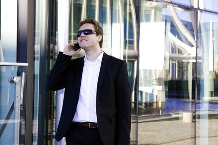 Young businessman outside modern office on the phone