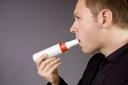 An adult male is blowing in a peak flow meter to test his lungs