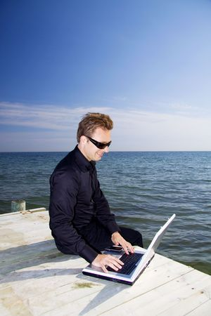 Business man using his laptop while sitting on the pier