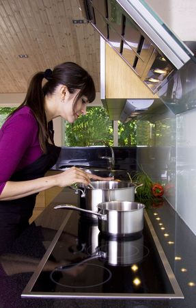 Woman stiring in a saucepan in a modern kitchen Stock Photo