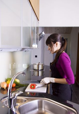 Cute woman slicing a red pepper Stock Photo
