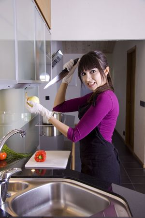 stabbing: Angry woman in kitchen stabbing an onion Stock Photo