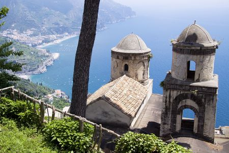 The Ravello garden offers a view of the two church towers, a tree and the Amalfi coast
