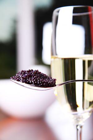 Zwarte kaviaar op een lepel naast een glas champagne