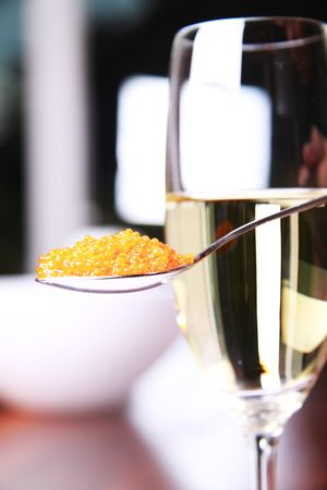Red caviar on a spoon next to a glass of champagne photo