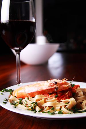 Shrimp pasta on a white plate served on a mahoney table Stock Photo