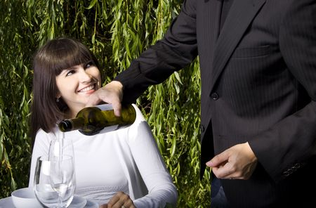 Waiter filling a glass of white wine for a woman dining in a garden Stock Photo