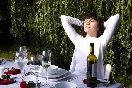 Beautiful woman is enjoying wine and the sun in a garden Stock Photo