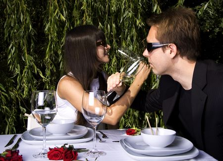Couple having a romantic lunch in the garden enjoying wine photo