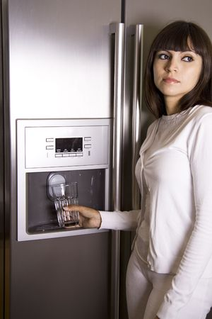 Pretty brunette in front of a modern refrigerator getting water and ice cubes