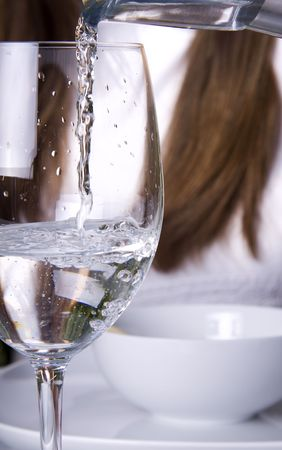 Pouring water into a glass into a wine glass photo