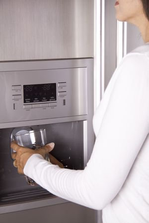 Close-up of a person getting water and ice from a modern refrigerator