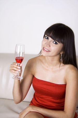 Woman having red drink on a sofa at a party Stock Photo