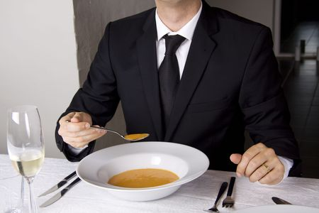 Business man is having lunch at a frensh gourmet restaurant. He is having lobster soup. Stock Photo