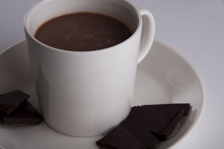 tasteful: Hot chocolate in a white cup with peices of dark deluxe chocolate on the side Stock Photo