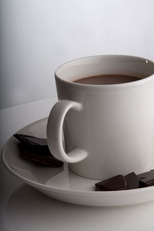 Hot chocolate in a white cup with peices of dark deluxe chocolate on the side Stock Photo