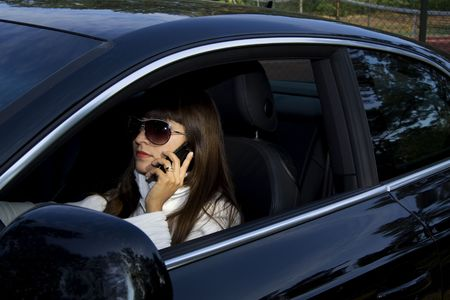 Beautiful woman driving a luxury car and talking in a cell phone Stock Photo