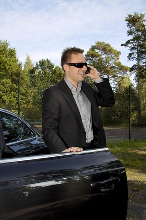 Business man is talking on the cell phone while standing next to a luxury car