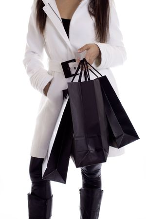 Stylish woman in a white coat with black shopping bags photo