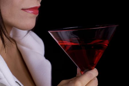 Woman with a red cocktail wearing a white coat Stock Photo