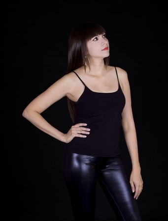 Beautiful brunette in black skin pants and a black shirt against a black background photo