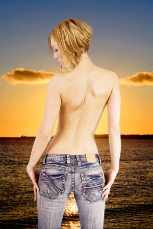 Natural blond woman standing on a beach looking at a sunset photo
