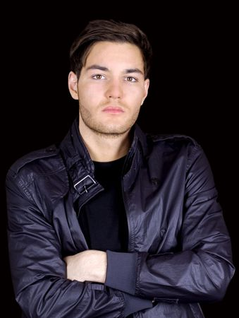 Young man in a leather jacket standing with arms crossed photo
