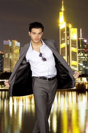 Young man in a grey suit in front of a skyline by night