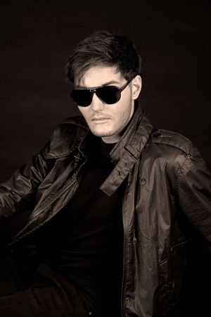 Cool young man in black leather jacket and sun glasses photo