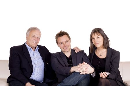 A senior couple and their adult son sitting in the sofa Stock Photo