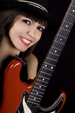 Woman with black hat playing country music on guitar photo