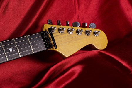 Close-up on an electric guitar on red satin background Stock Photo