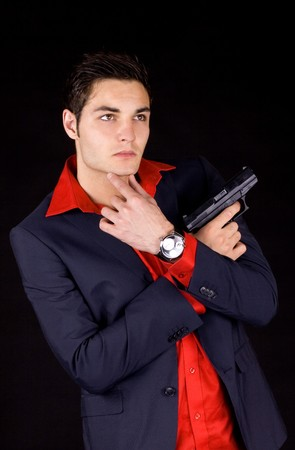 Young wise guy in a suit and red shirt holding a gun