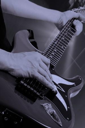 Man playing an electrical guitar at a rock concert photo
