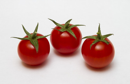 Three tomatoes on a white background Фото со стока