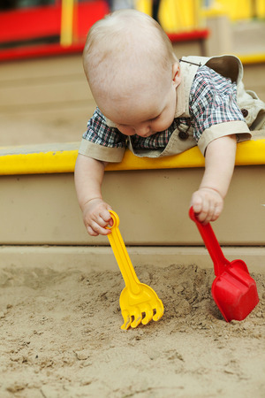 splotchy: little blond toddler sitting in a sandbox with a yellow and red shovel  Stock Photo