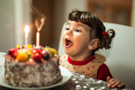 memorable: little girl blows out the candles on the cake in her birthday