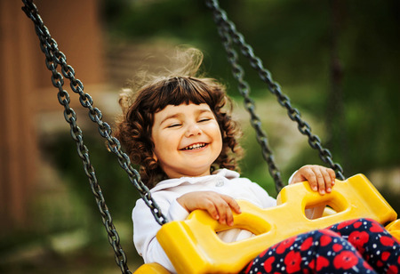 naughty or nice: cute little curly girl riding on a swing, laughing