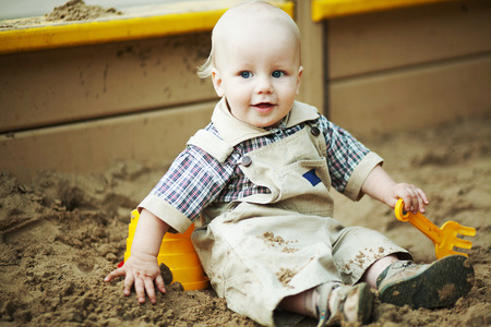sitt: blond little boy sitting in a sandbox with a shovel and bucket and smiling
