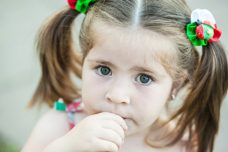 attentiveness: little girl with hair tails looking with seriousness and surprise Stock Photo