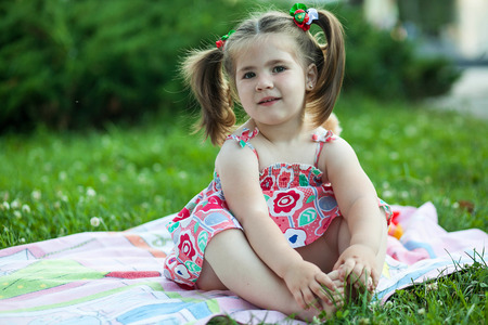 cute little chubby girl sitting on a mat in nature among flowers