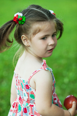sitt: chubby little girl playing in nature and is holding an apple