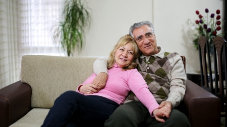 Senior couple sitting on sofa photo